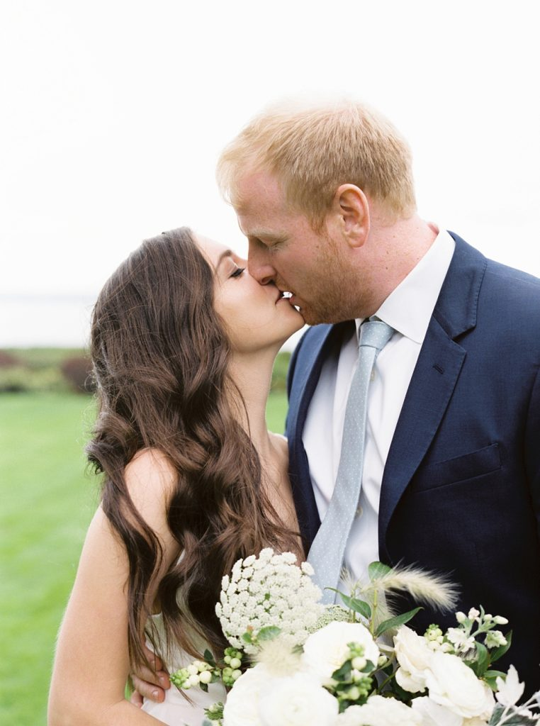 bride and groom kissing during portraits after first look on private estate