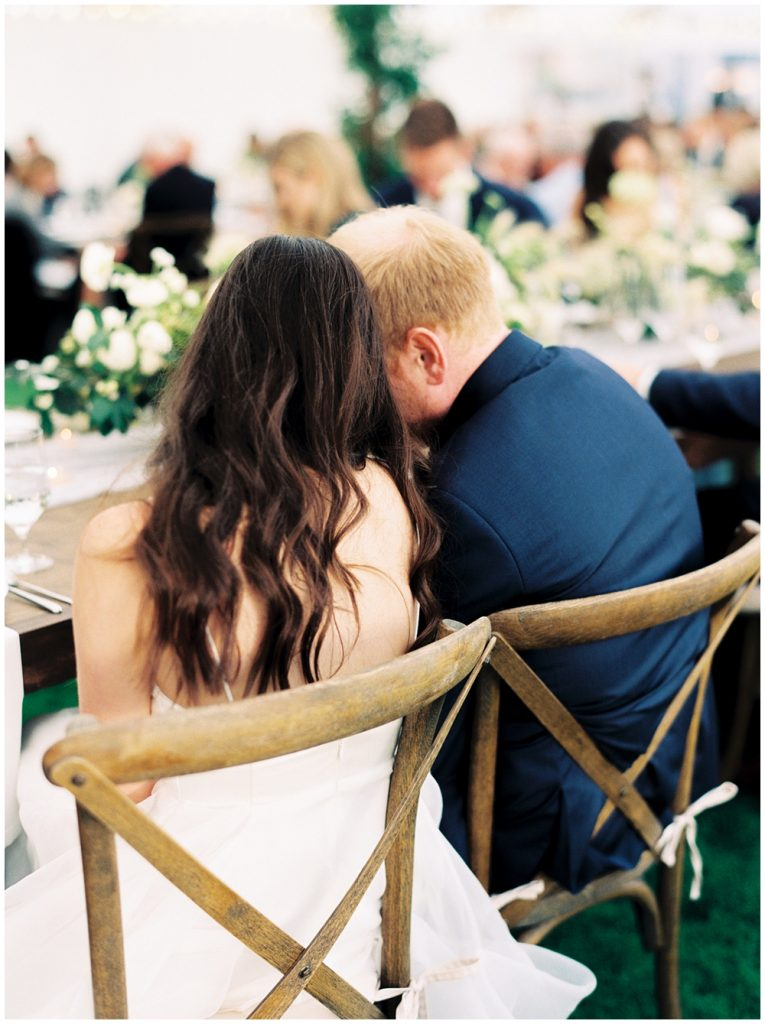 Bride and groom foreheard to forehead during the toasts, sitting in cross back chairs
