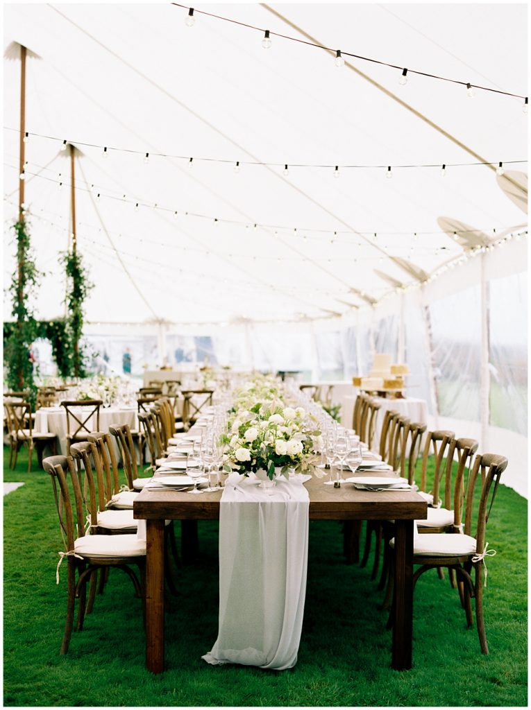 Lengthwise shot of the head table under a sail cloth tent set up for the reception with a table runner and cross back farm chairs