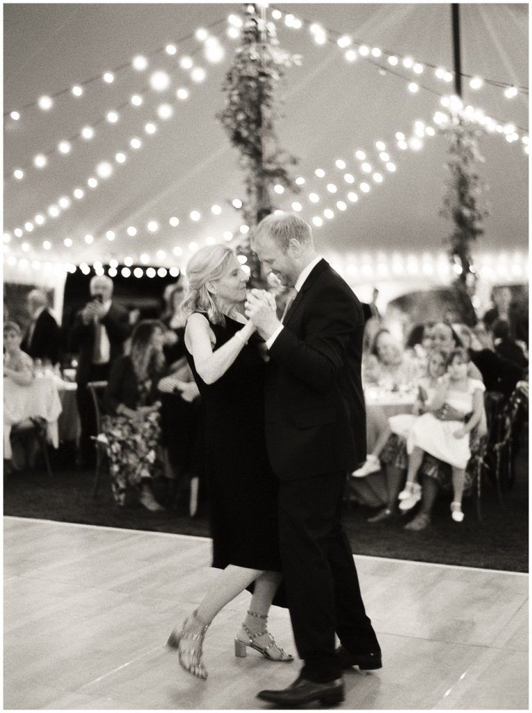 Mother son dance in front of guests under string lights at sail cloth tent, private estate reception