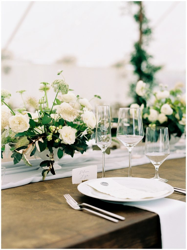 Head table place setting set with menu, centerpieces and glasses for each type of wine as well as champagne under a sail cloth tent