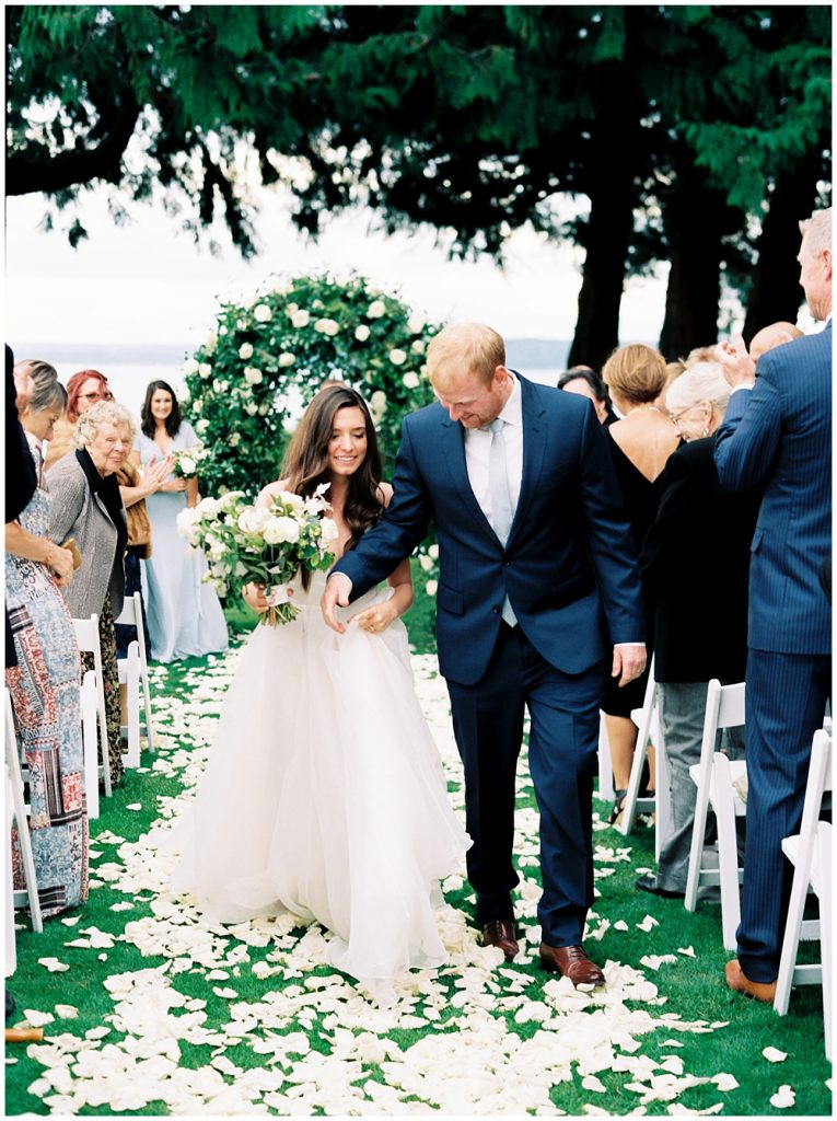 bride and groom walk back down the rose petal covered aisle during the recessional