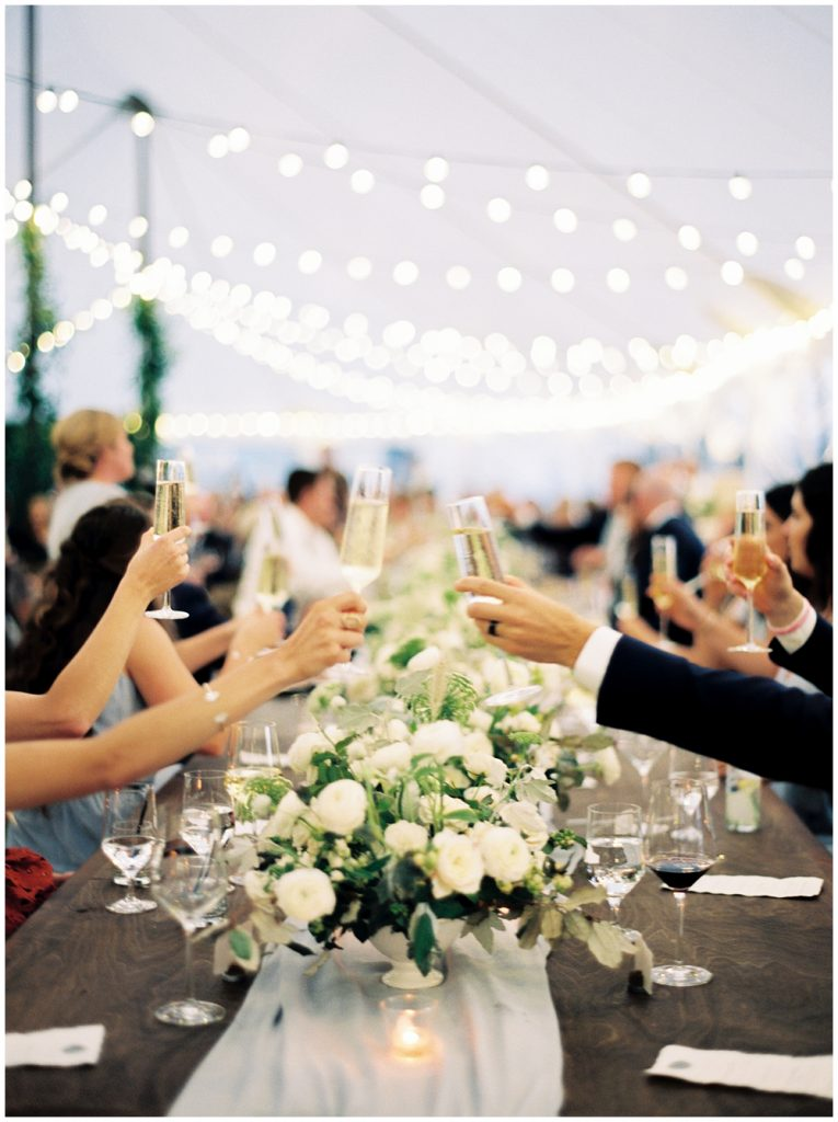 Toasts across the head table under string lights and over candlelight