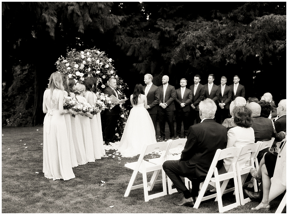 black and white photo of ceremony while everyone is at the alter and guests look on