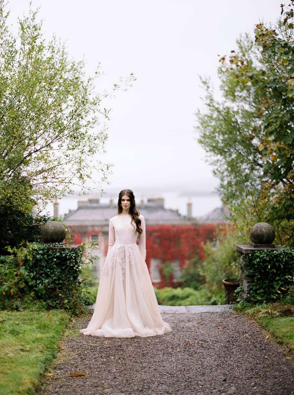 Bantry Ireland bride standing in Cathy Telle Gown at the top of the garden stairs overlooking Bantry House