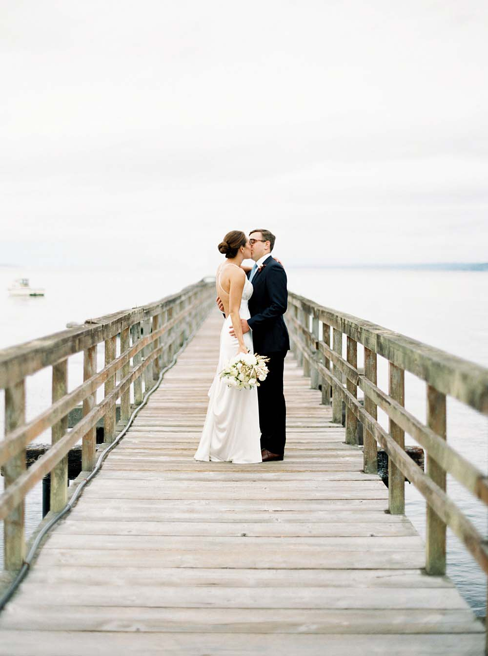 Bride and groom standing alone on a private dock, kissing
