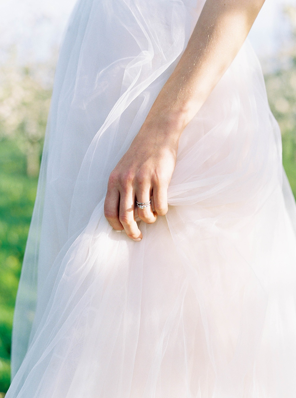 Closeup of bride holding wedding dress