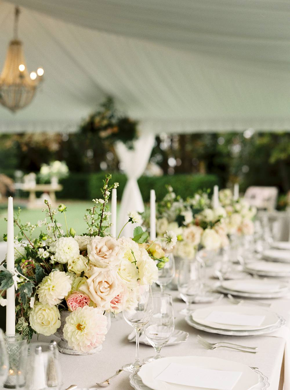 Shot of tented wedding reception highlighting the blush and white floral arrangements and placesettings.