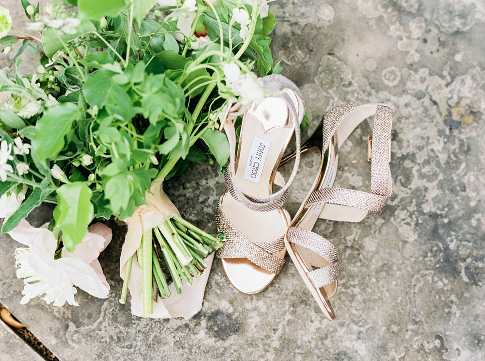 A pair of Jimmy Choo heels with a green floral bouquet.
