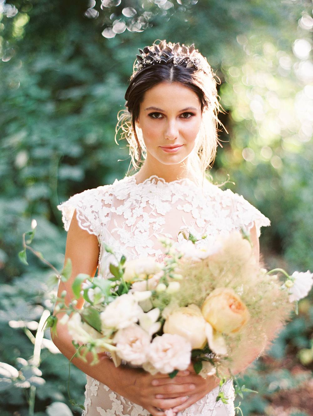Gorgeous summer bride backlit by evening sun in a forest, holding a beautiful white and blush floral bouquet.