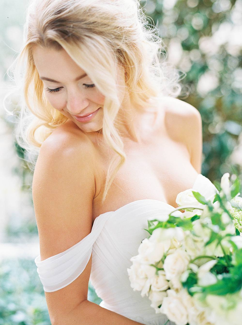 Beautiful bride smiling over shoulder, holding white and green floral bouquet.