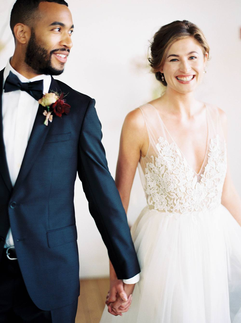 Mixed race bride and groom holding hands and smiling post wedding ceremony.