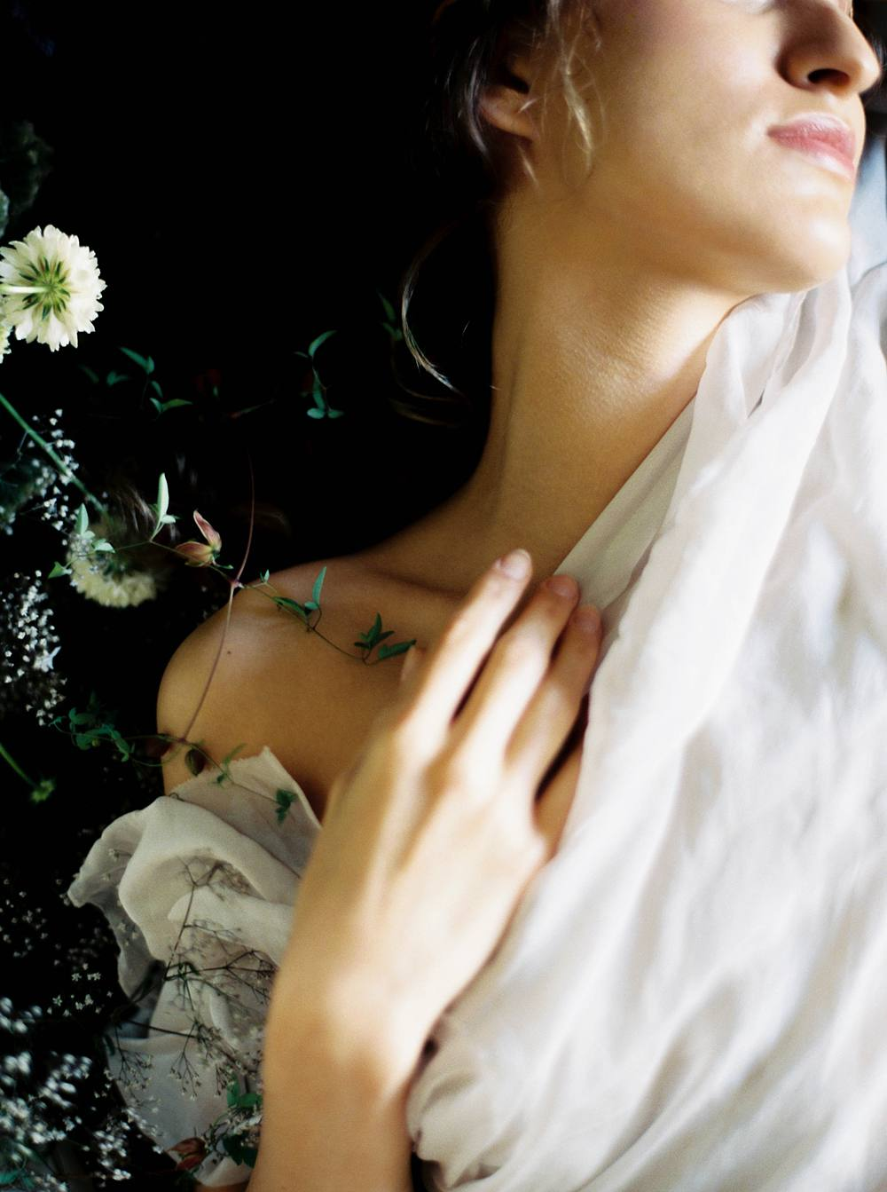 A close in crop of a boudoir session with a woman wrapped in soft fabric, touching her collar bone with her fingertips.