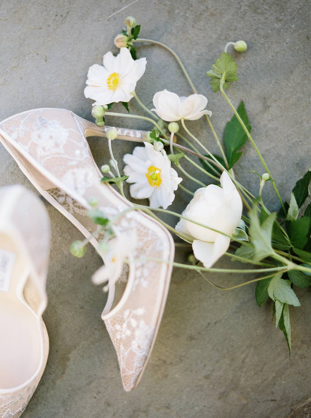 Close-up of Jimmy Choo's bridal heels resting with a small bouquet of white flowers.