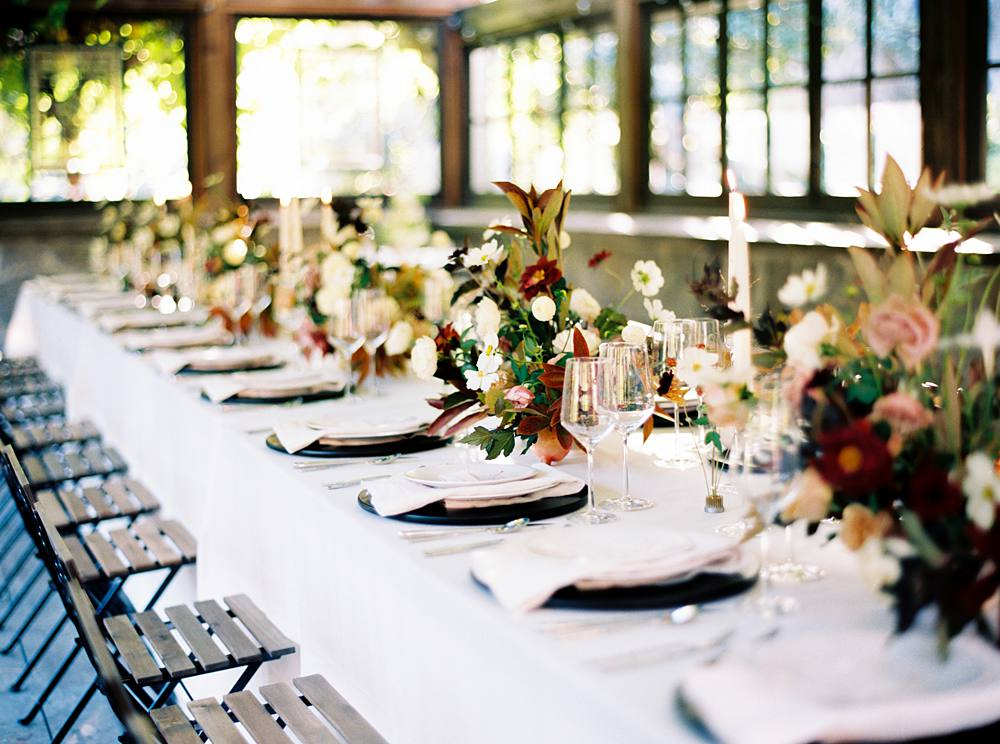 Shot looking down the wedding reception table in a grape house with autumn styled centerpieces.