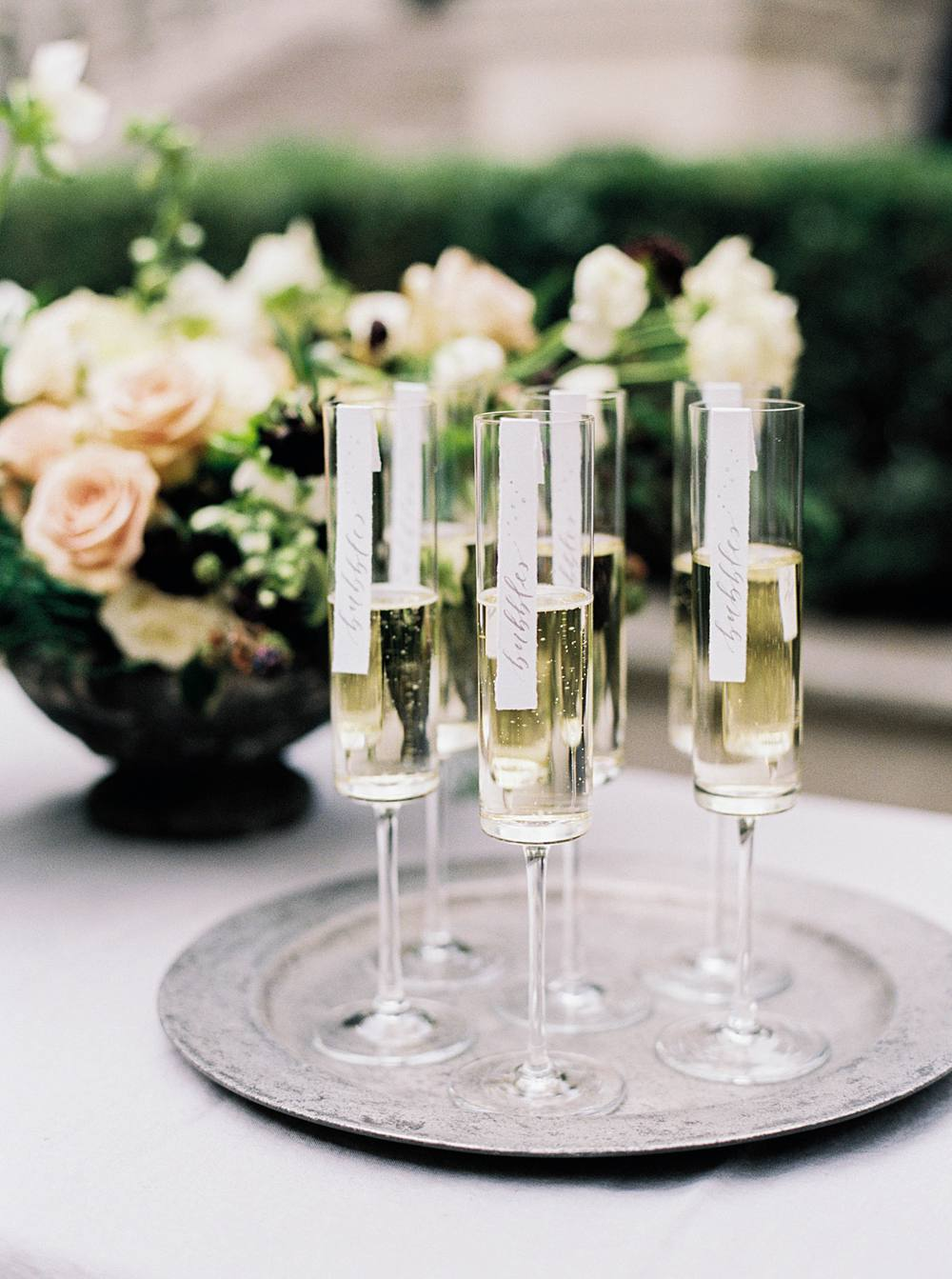 Close-up of champagne flutes with custom name tags hanging from rim.
