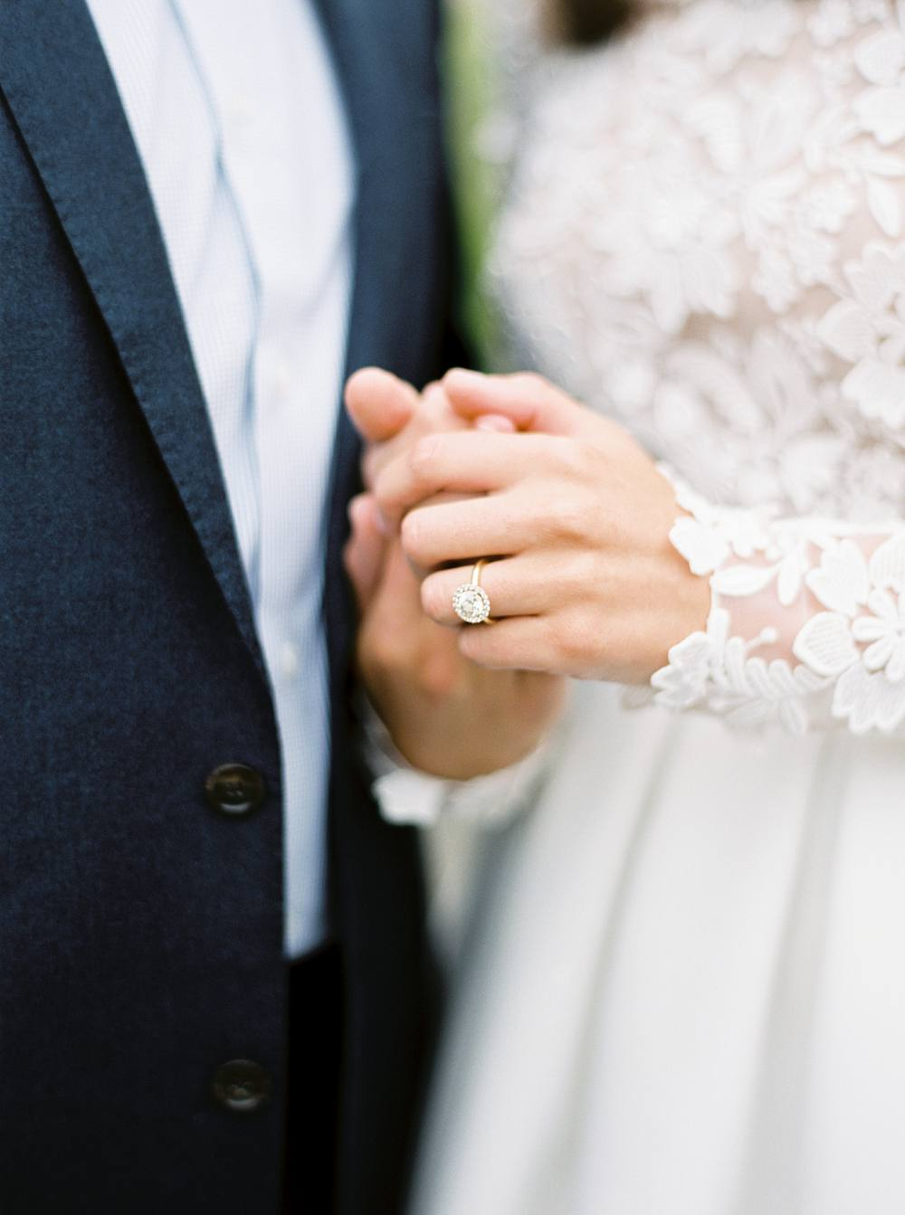 Close-up of bride and groom's hands, highlighting engagement ring and Rime Arodaky dress.