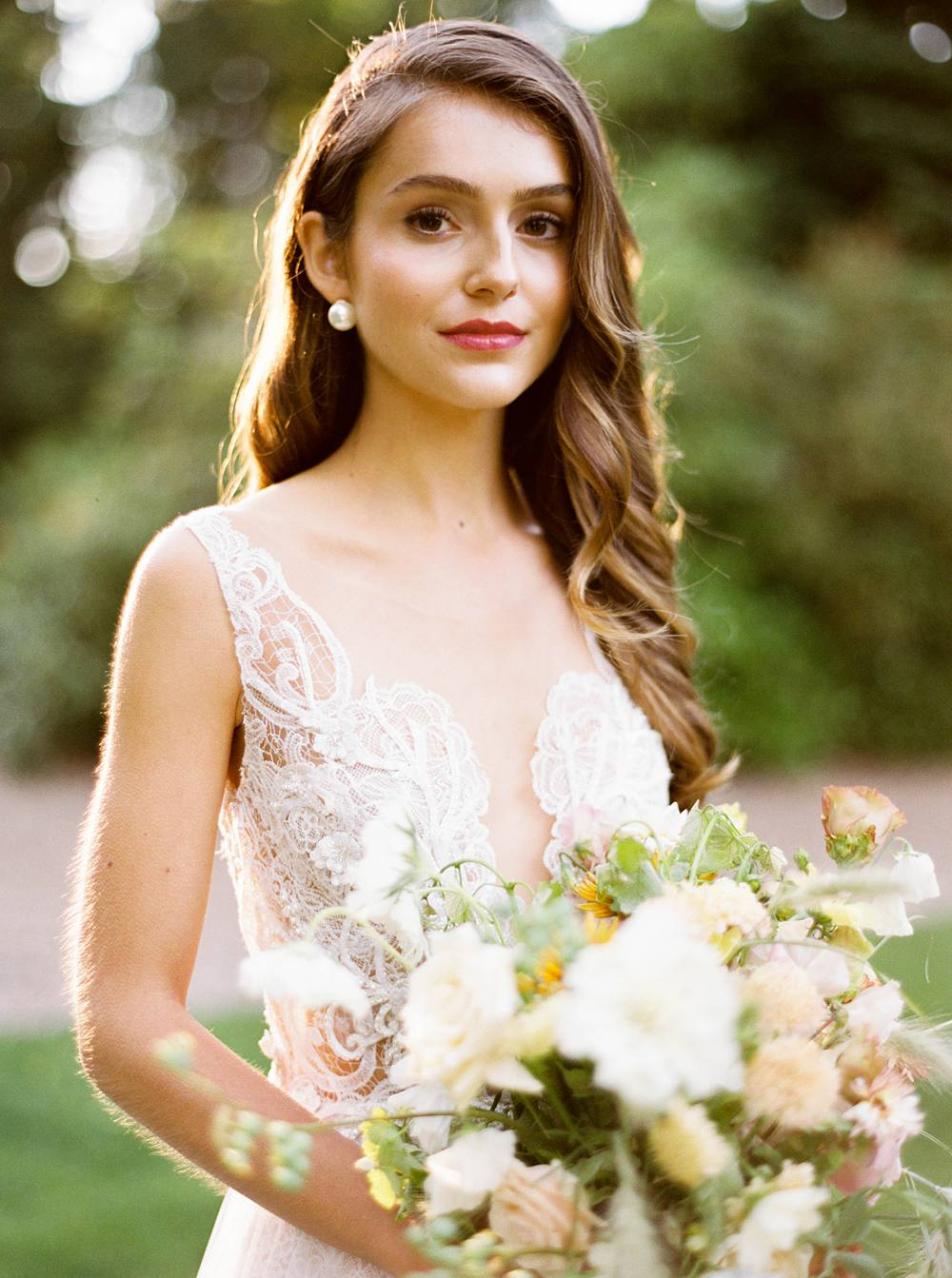 A stunning bride glows in the golden summer light while holding a pink and white floral bouquet.