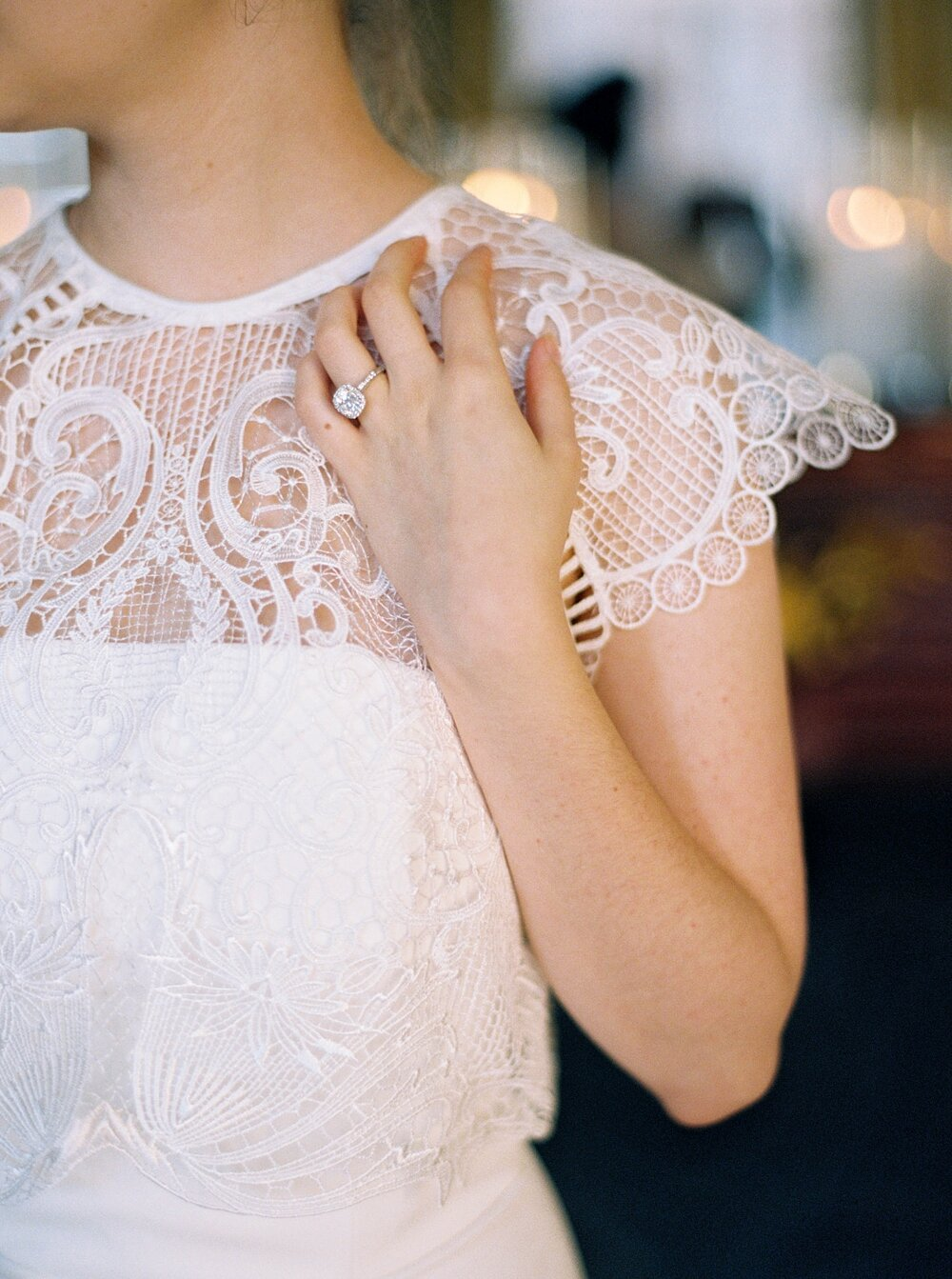 Ring detail shot, bride's hand against her collar bone with a lace top over her wedding gown