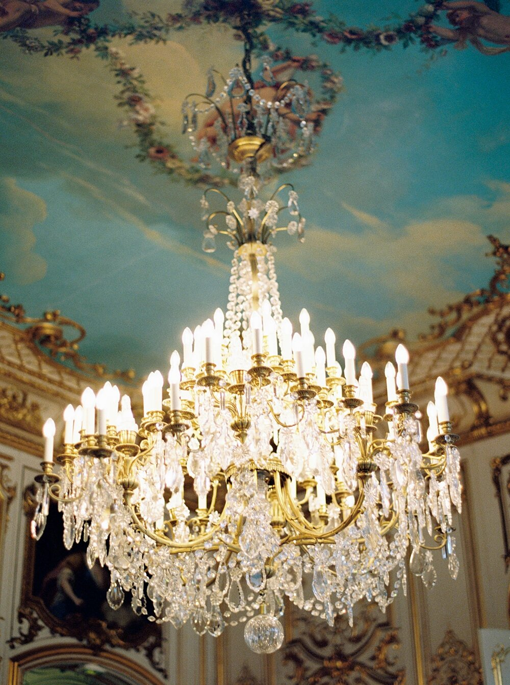 Chandelier against ceiling painted blue with adornments at Hotel Le Marois in Paris, France