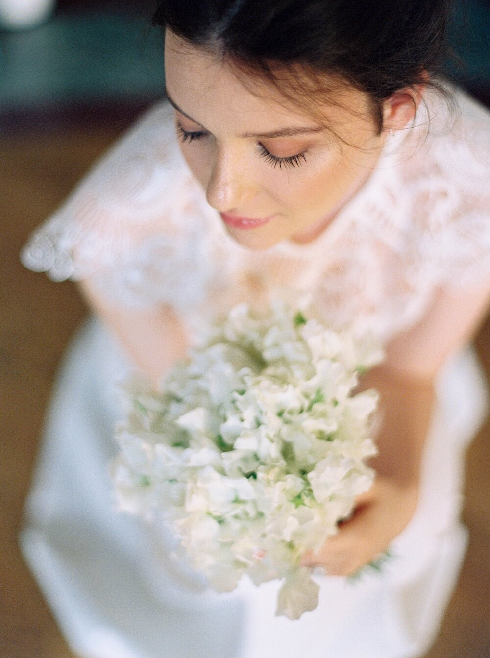 Overhead shot of Bride with a bouquet of white sweet peas in her hands