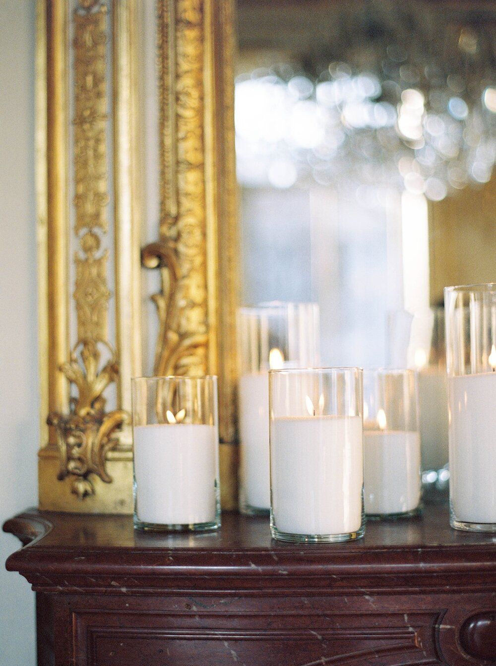 pillar candles on the mantlepiece in front of a gold gilded mirror