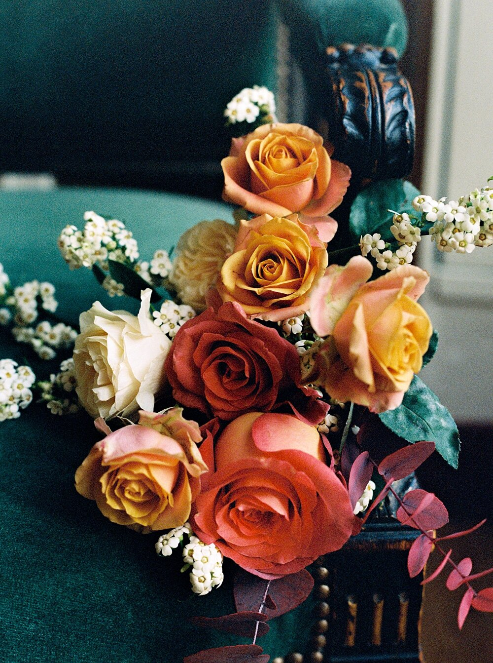 Fall rose bouquet with orange and red roses sitting on an emerald velvet chair