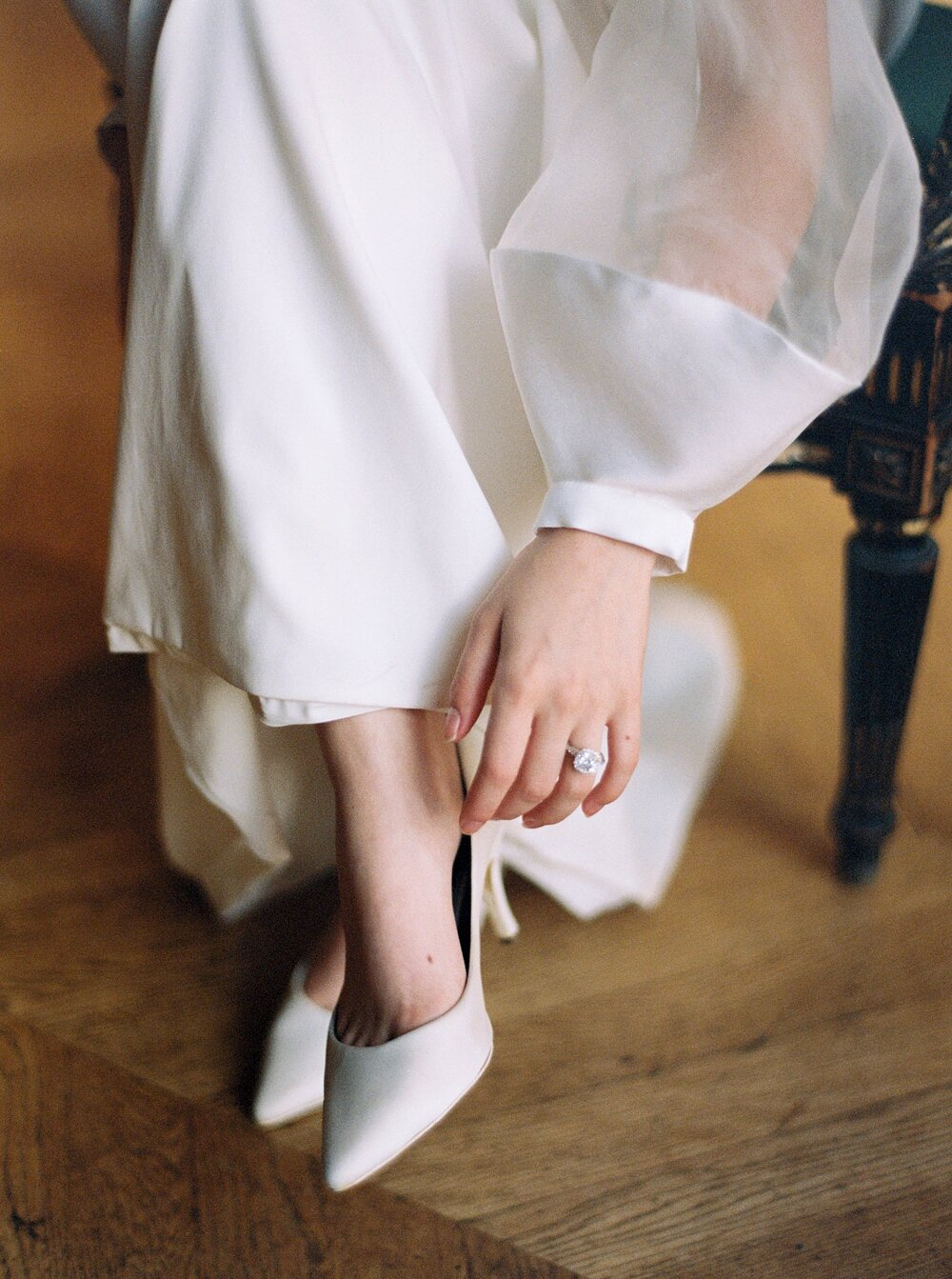 Bride's hand touching her shoe as if she's put it on recently, showing off her engagement ring