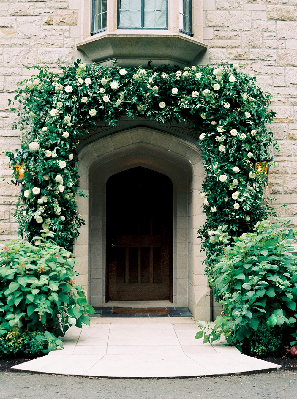 Arch of greenery and white flowers over the front door of the private estate overlooking the puget sound