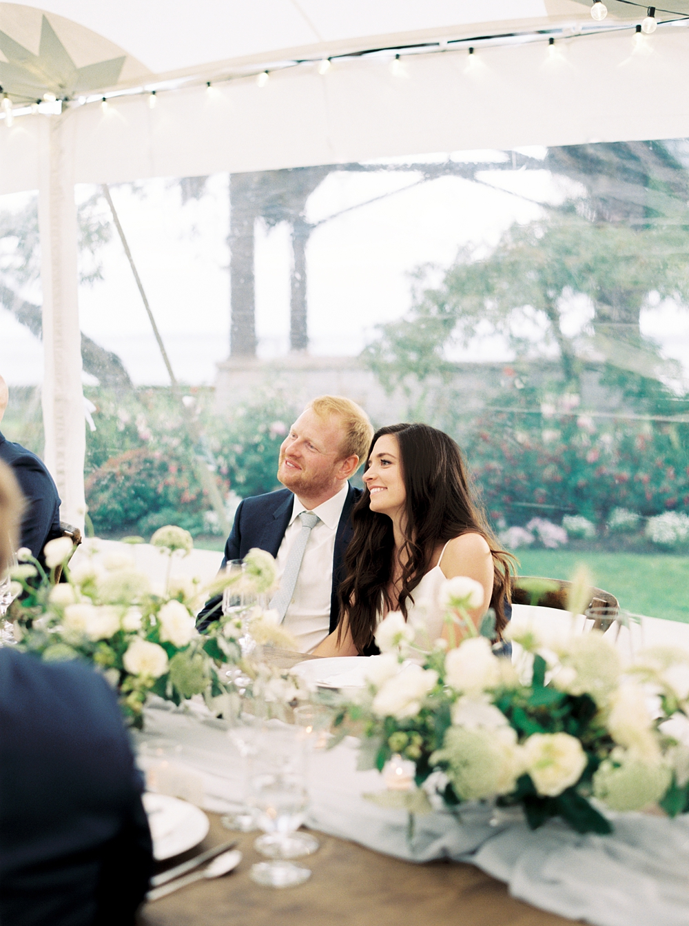 bride and groom smiling and sitting at the head table during toasts