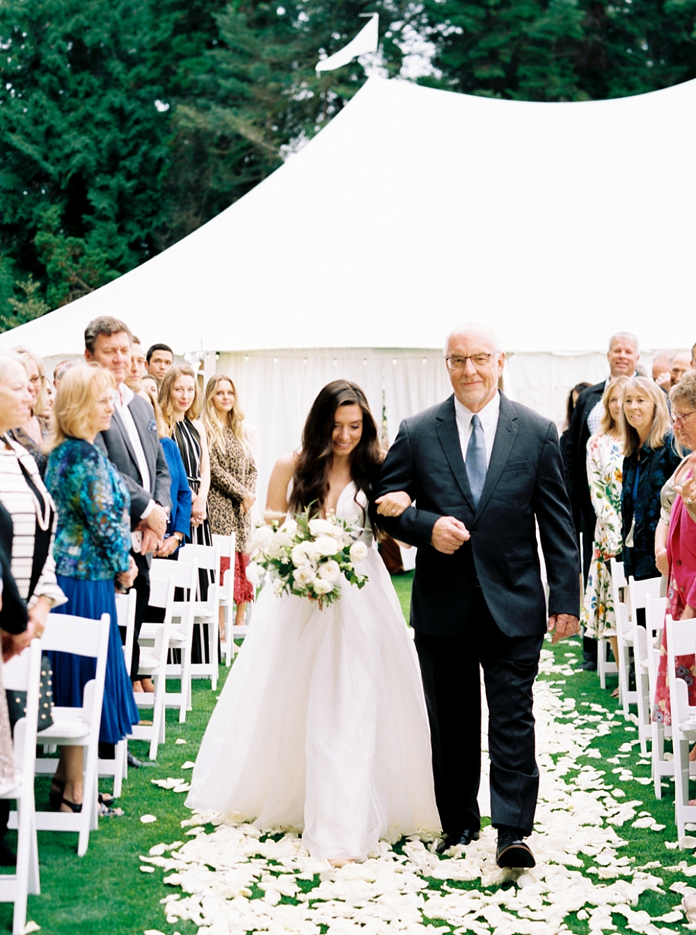 Bride walking down the aisle with her father, sail cloth tent in the background, white rose petals on the ground