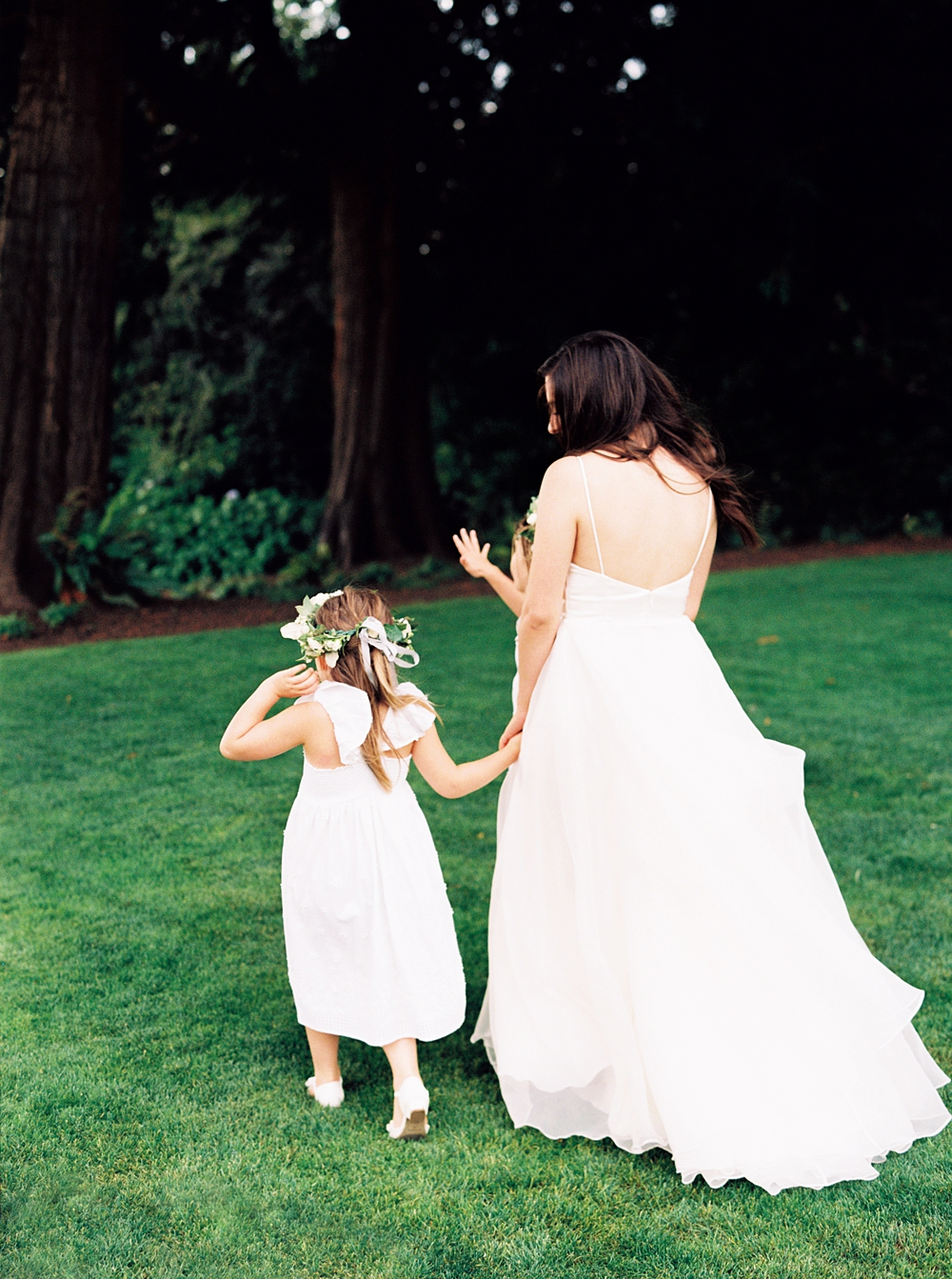 Bride walking with the flower girls, heading to the edge of the property to take pictures before the reception