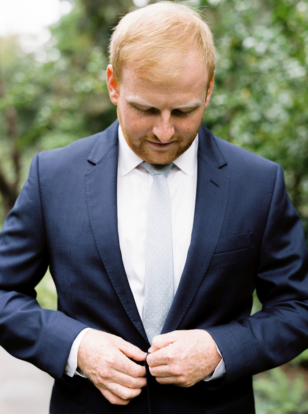 Portrait of the groom buttoning his jacket