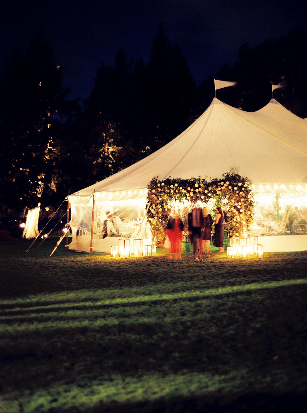 outside of the tent after dark, lit up by twinkle lights and candles