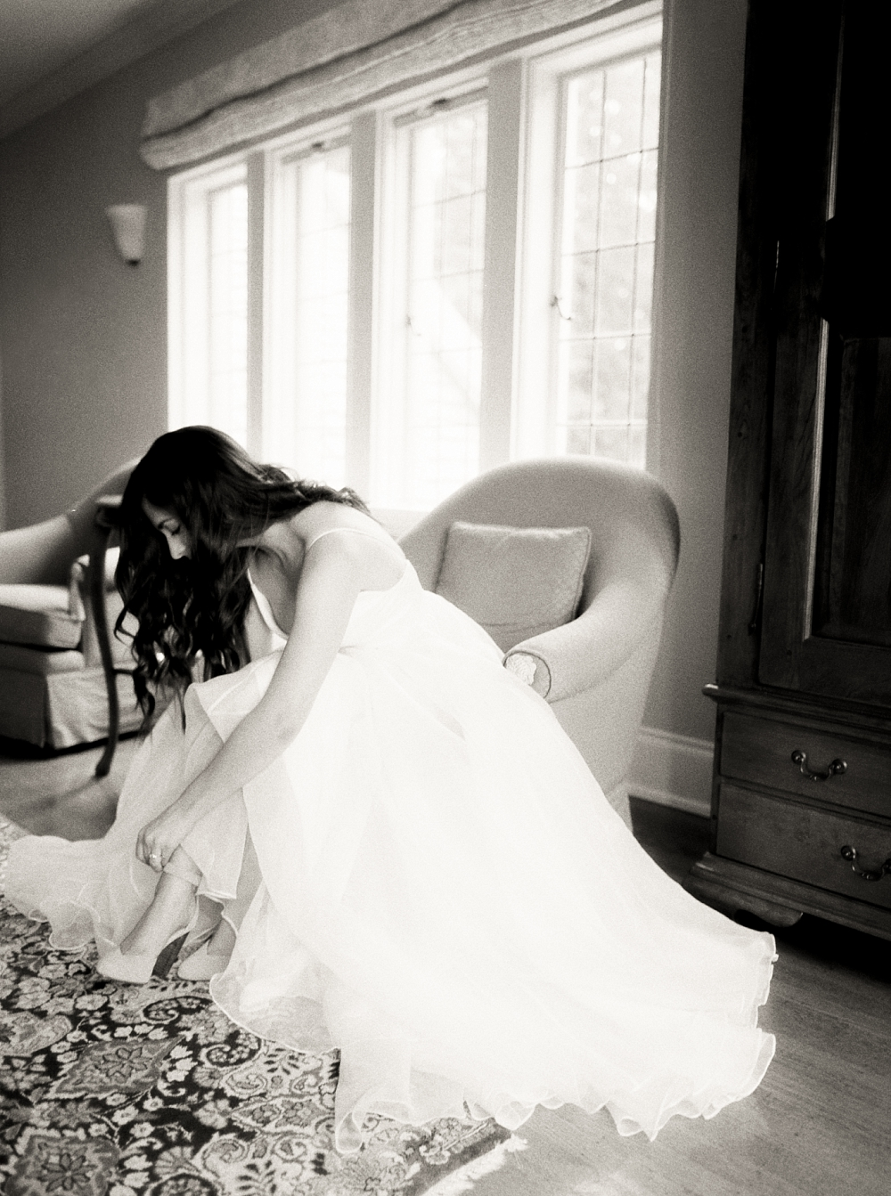 Black and white portrait of bride putting her shoes on