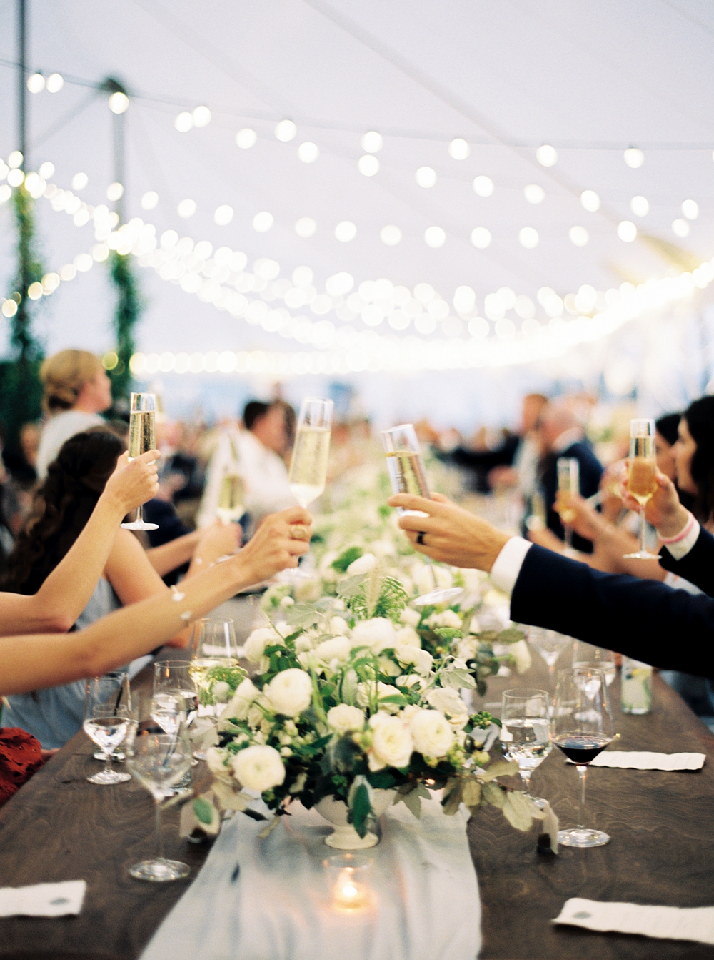 champagne flutes held up across the head table for toasts