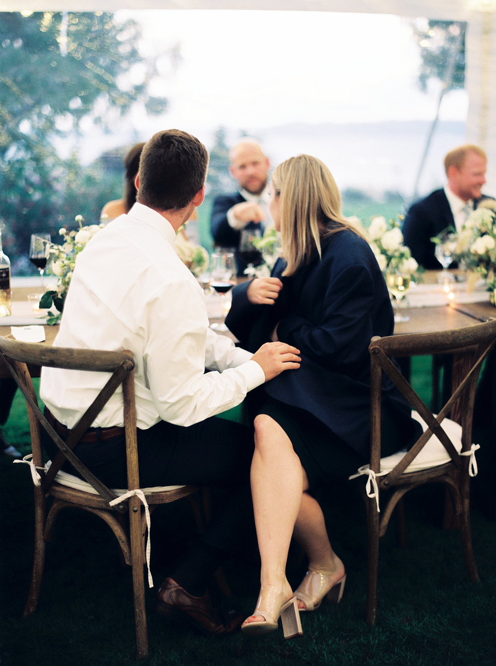 bridal party member sitting at the head table during reception, bridesmaid wearing groosman's jacket